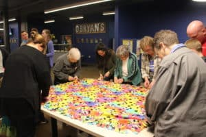 Sister Marcella Schrant, second from left, Sister Judith Nell Riney, fourth from left, Sister Sharon Sullivan, right, and others are nearly done with a puppy-themed children's blanket.