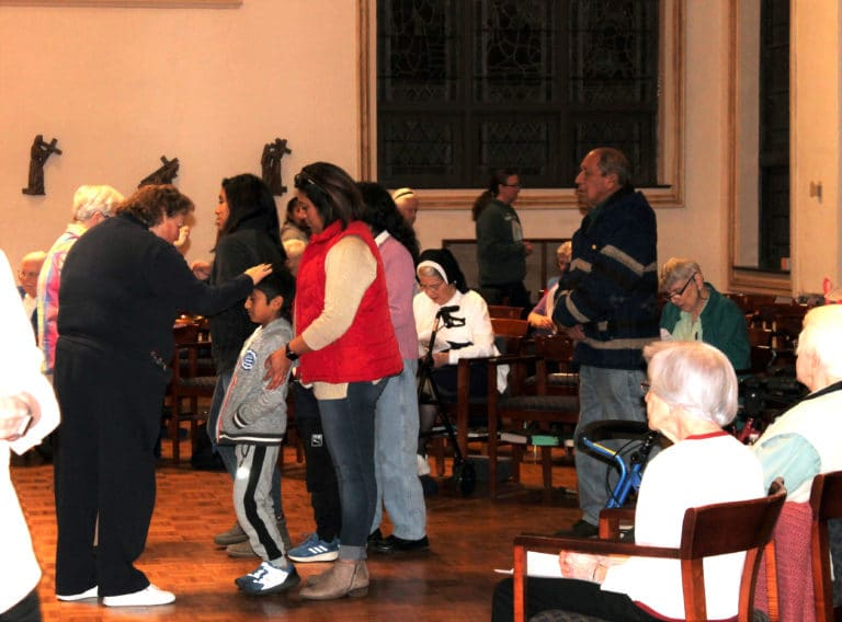 Sister Alicia Coomes blesses a child in the line for the Eucharist.