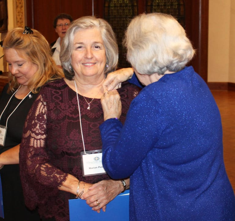 New Associate Marian Pusey receives her Associate pin from Pauline Goebel, with new Associate Lori Haynes at left.