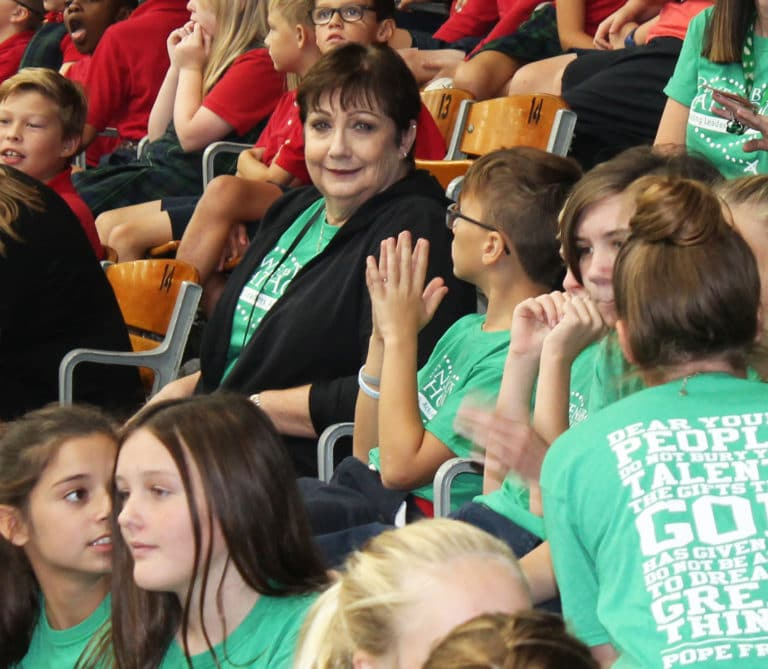 Ursuline Associate Bonnie Marks gathers with her students from the Owensboro Catholic 4-6 Campus.
