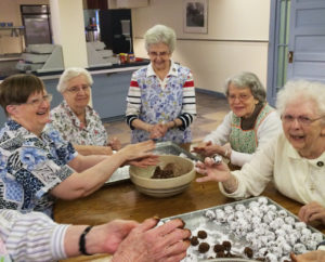 A mysterious set of hands is a bit chocolatey as this happy bunch keeps making bourbon balls. From left are Sisters Rebecca White, Eva Boone, Naomi Aull, Catherine Barber and Mary Agnes VonderHaar.