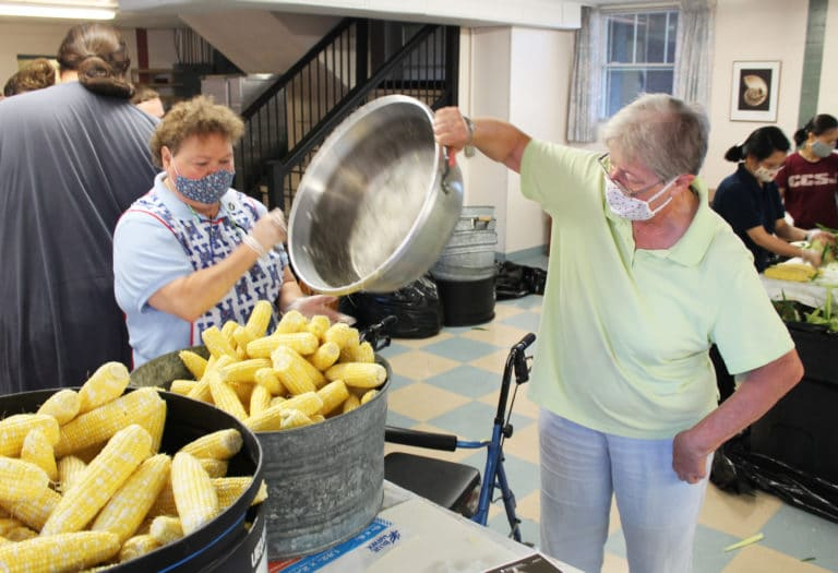 Sister Alicia Coomes, left, and Sister Emma Anne Munsterman empty a pan of sweet corn into a bucket to be taken to the kitchen. The corn is blanched, frozen and served to the Ursuline Sisters and staff throughout the year at mealtimes.