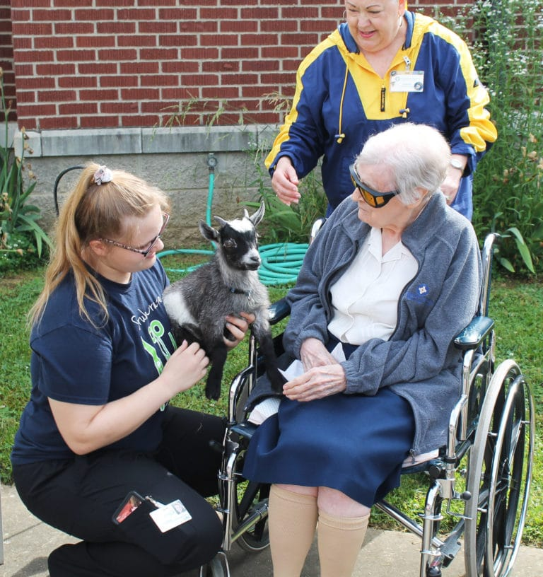 Sister Marie Goretti Browning meets Elvis the goat, while Donna Nelson and Debbie Dugger stand by.