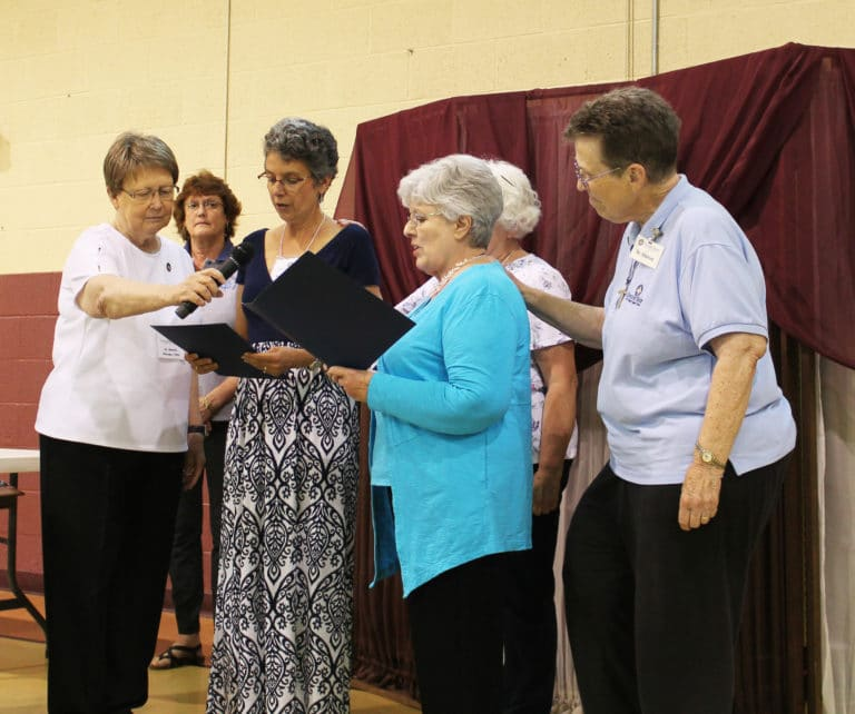 Sister Amelia Stenger, left, holds the microphone as Maryann Joyce, center, and Mary Alice Wethington read their Associate commitments. Sister Sharon Sullivan, right, was the contact person for Mary Alice.