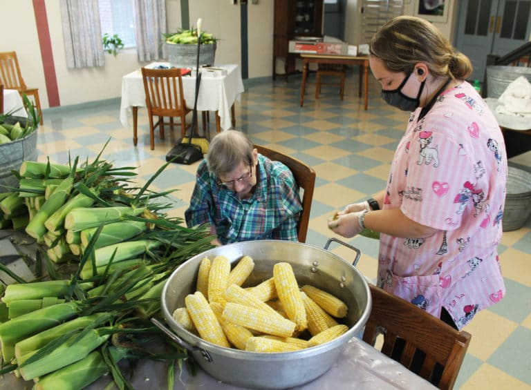 Sister Susanne Bauer, seated, and Food Services employee Alexis Thompson work intently on shucking freshly chopped corn.