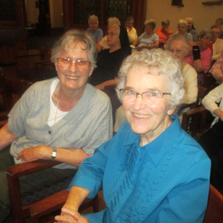 Sister Mary Ellen Backes, left, and Sister Ann Patrice Cecil gather in the Motherhouse Chapel for the opening session July 10.