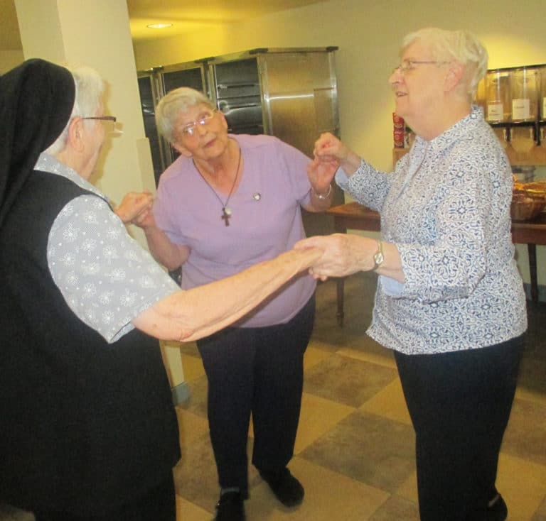 While listening to some live music performed by Dennis Mayfield, Sister Mary Celine Weidenbenner, center, leads Sister Michael Ann Monaghan, left, and Sister Eva Boone in an impromptu jitterbug.
