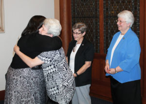 Sister Stephany gets a hug from Sister Pam Mueller, as Sister Judith Nell Riney, center, and Sister Pat Lynch look on. The three sisters are on the Leadership Council.