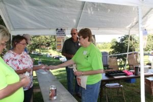 Gene Lyon hands out pull tabs to visitors at the picnic.