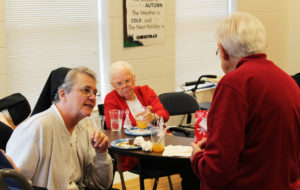 Sister Michael Marie Friedman, left, chats with Sister George Mary Hagan as Sister Mary Jude Cecil puts down her drink.