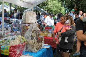 Visitors look at more than 140 baskets up for bids in the Silent Auction booth.