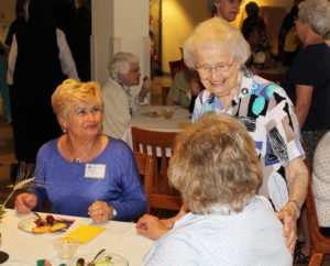 Sister Alfreda Malone, standing, talks with Ursuline Associate Suzanne Reiss, as Associate Carol Hill, left, looks on.