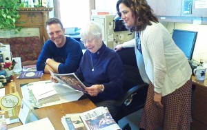 Sister Marcella Schrant, center, looks over the newspaper with two of her companions at St. John the Evangelist Parish in Lawrence, Kan. At left is Peter Haack, a musician who also prepares the bulletin, and at right is Nicki Daneke, who works with Catholic Charities.