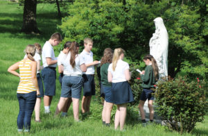 "The students take notes at the Saint Theresa of Lisieux statue in the front of campus as part of the scavenger hunt. Saint Theresa is known as ""the little flower."""